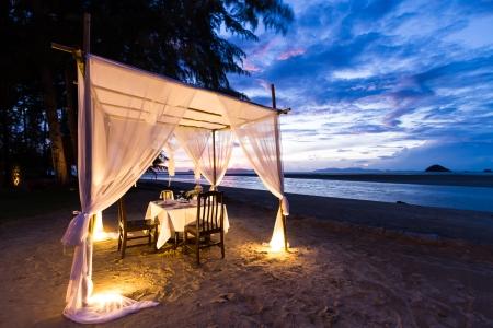 lãng mạn: thiết lập bữa ăn tối lãng mạn trên bãi biển trong khi hoàng hôn