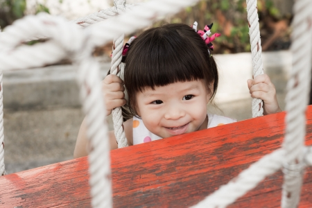 jungle gym: smiling girl hiding behind jungle gym