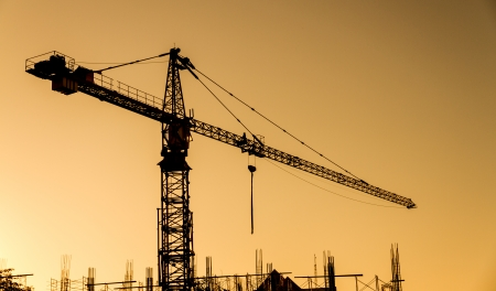 crane tower: crane at construction site while sunset