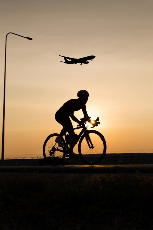 man biking with plane above while sunset