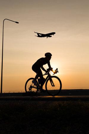man biking with plane above while sunset
