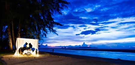romantic dinner: configuration de dîner romantique sur la plage tandis que le crépuscule