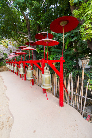 walkway in temple decorated with golden bell and red umbrella photo