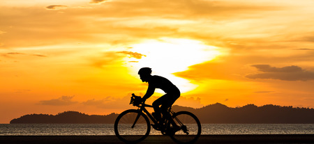 man biking his bicycle on the beach with sunset view  photo
