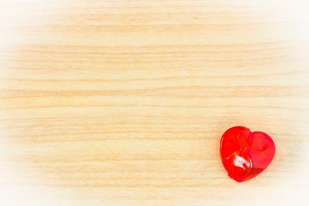 plastic heart: rosso a forma di cuore di plastica su sfondo legno
