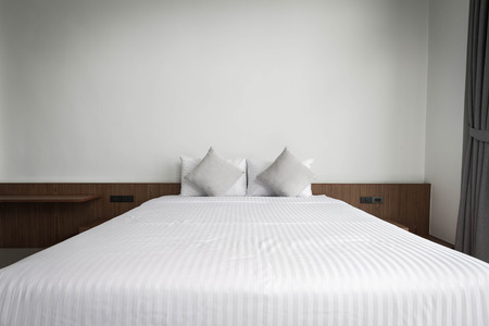 bedsheet: white clean bedsheet on bed with pillows in bedroom