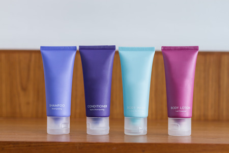 colorful tubes of bathroom amenity contains of shampoo, conditioner, shower gel, body lotion photo