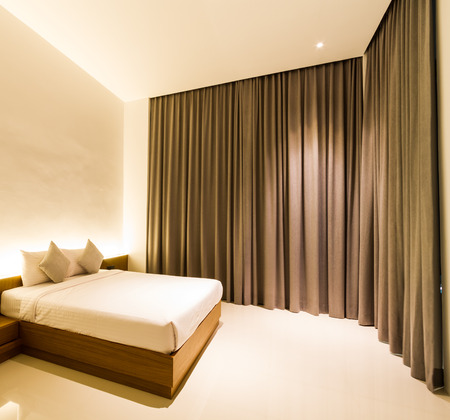king size bed: king size bed in square bedroom with brown curtain