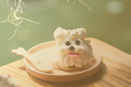 treat like a dog: sponge cake decorating as dog in warm tone Stock Photo