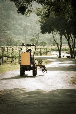 man driving yellow mini tractor in vinery yard photo