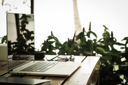 laptop and sunglasses on wood table in garden