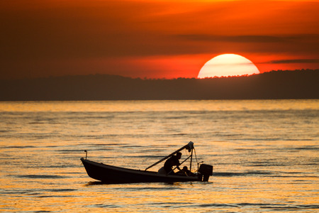 big sunset and boat in the sea