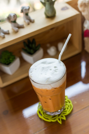 glass topped: glass of iced milk tea topped with steamed milk