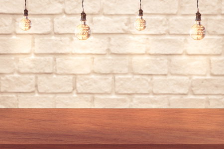wood blocks: edge of wood table and white brick wall background with light bulbs