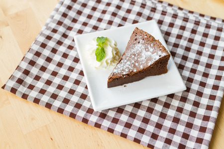 flourless chocolate cake: piece of flourless chocolate cake on white square dish Stock Photo