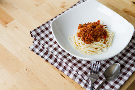 menu design: spaghetti bolognese on white square dish served on wood table Stock Photo