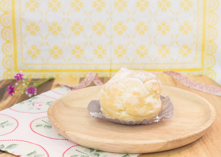 choux bun: piece of choux cream on wooden plate Stock Photo