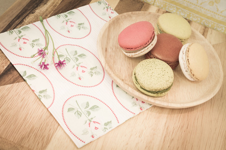 colorful macarons served on wooden dish