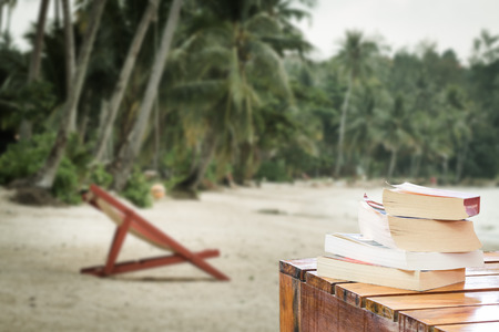 relax beach: pile of books on wood table at the beach Stock Photo