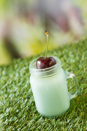 summer pudding: fresh cherry on green tea pudding in grass background