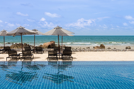 poolside: black daybeds and umbrella at poolside with sea view