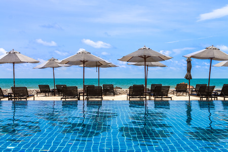 daybed: black daybeds and umbrella at poolside with sea view