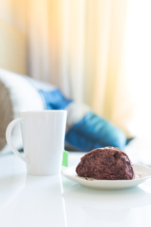 daybed: riceberry bread and cup of tea on white table beside sofa