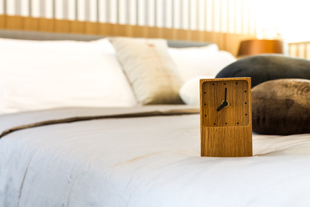 wooden clock: square wooden clock on bed