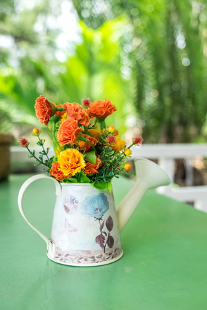 watering pot: colorful fabric flowers in watering pot decorated on table