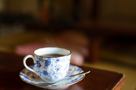 antique table: hot tea in vintage painted cup at japanese restaurant Stock Photo