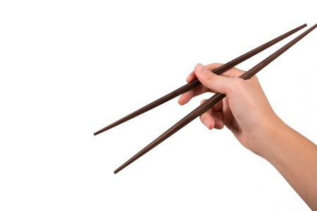 closeup woman hand holding wood chopsticks on white background Stock Photo