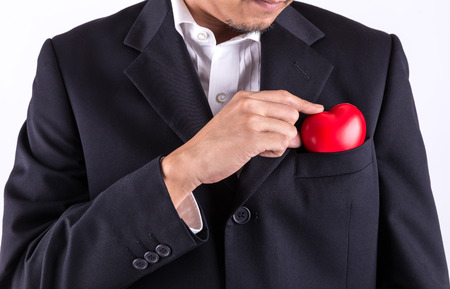 business service: part of man in black suit keeping red heart in pocket Stock Photo