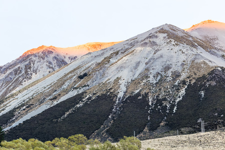 incidence: golden mountain peak from sunrise at Arthurs Pass, New Zealand