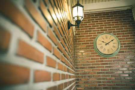 classic clock and lamp on brick wall