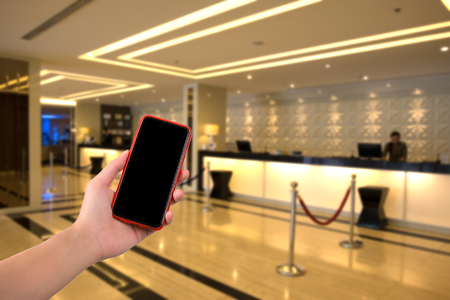 reception counter: woman hand holding smart phone with hotel reception counter on background