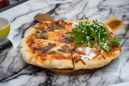 half and half pizza, smoked salmon and mixed meat, topped with rocket vegetable served on table