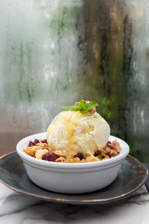 apple crumble topped with vanilla ice cream in white bowl served on marble table