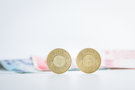 50 Taiwan dollar coins with banknotes on background