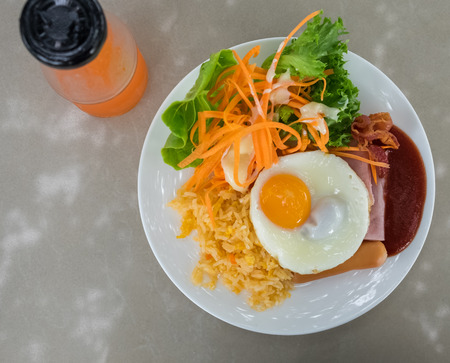 compose: breakfast dish compose of fried egg, fried, rice, ham, sausage, bacon, and salad with tomato sauce and fresh fruit juice