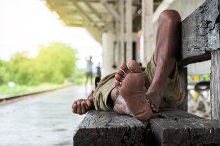 closeup homeless mans feet sleeping on wood bench at train station
