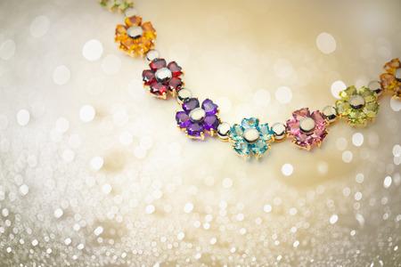green gemstone: colorful flowers gems necklace on shiny bokeh background Stock Photo