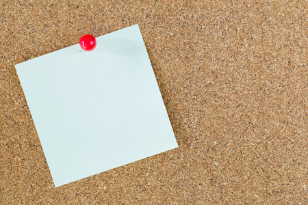 red pin on post-it note with cork board background