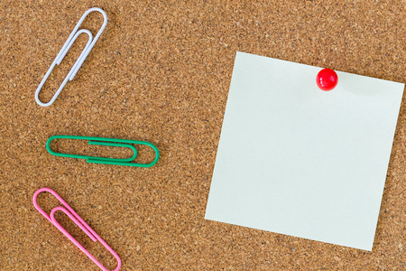 post-it note on cork board with red pin and colorful paper clips Stock Photo