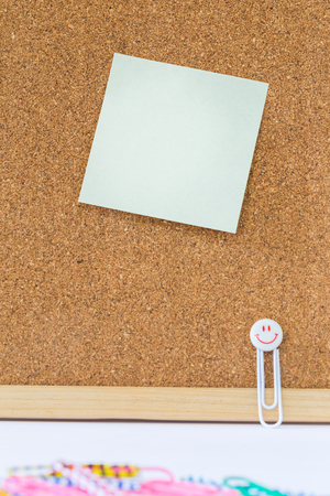 note paper and clips on cork board