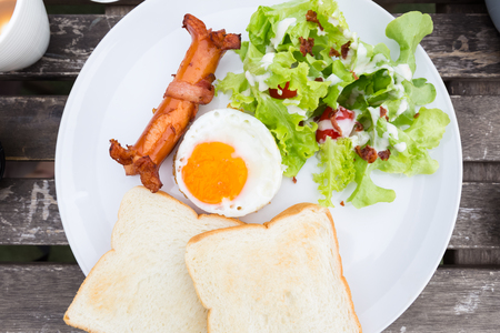 closeup breakfast dish composed of fried egg, sausage and bacon, salad, and toast