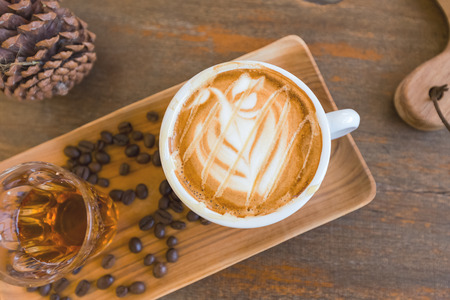 top view cup of hot coffee with latte art decorated with coffee beans