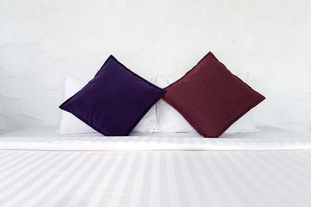 white clean bedsheet with colorful pillows in bedroom