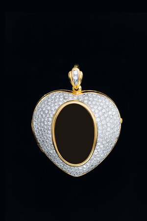 gold heart shape locket frame pendant with diamond on black background