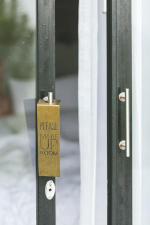 please make up room sign on opened resort door of messy room