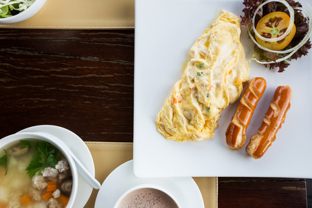top view of breakfast set at resort, omelette and sausage with rice congee